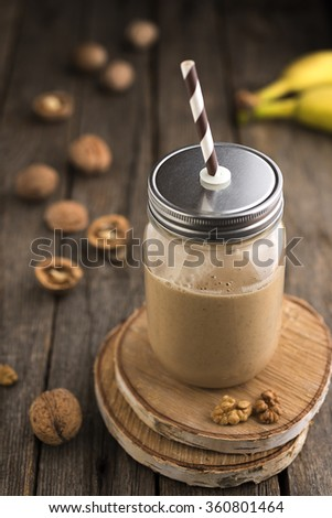 Banana walnut smoothie on old wood table - stock photo