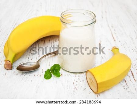 Banana yogurt and fresh bananas on a wooden background - stock photo