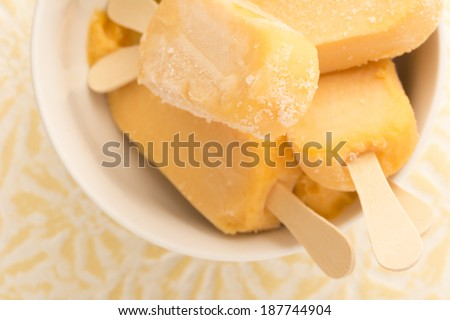 Banana, yogurt, mango popsicles with white bowl - stock photo