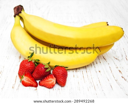 Bananas and strawberries on a old wooden background - stock photo
