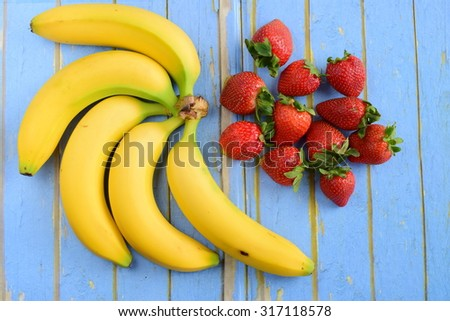 Bananas and Strawberries on Wooden Blue Background - stock photo