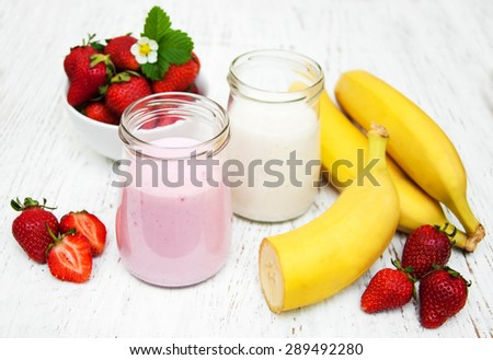 Bananas and strawberries with yogurt on a wooden background - stock photo