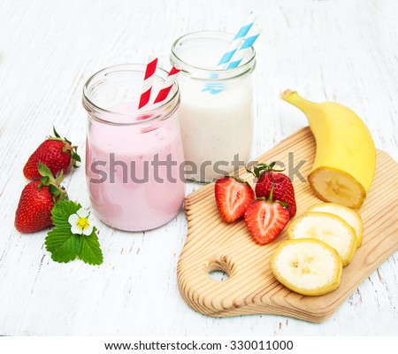 Bananas and strawberries with yogurt on a wooden background