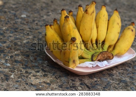 Bananas place on a pink plate on cement - stock photo