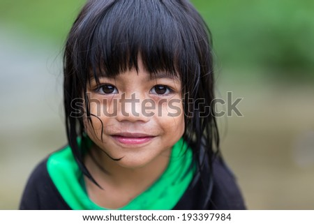 BANAUE, PHILIPPINES, DECEMBER 04 : A young unidentified Filipino little girl is posing under the rain in the village of Banaue, north Luzon, Philippines, on december 04, 2013 - stock photo