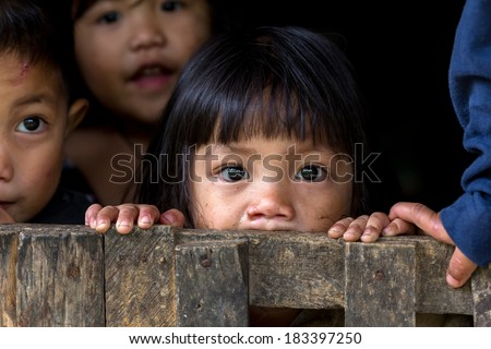 BANAUE, PHILIPPINES, DECEMBER 04 : An unidentified Filipino little girl with her brothers and sisters is staring at the camera in the village of Banaue, north Luzon, Philippines, on December 04, 2013 - stock photo