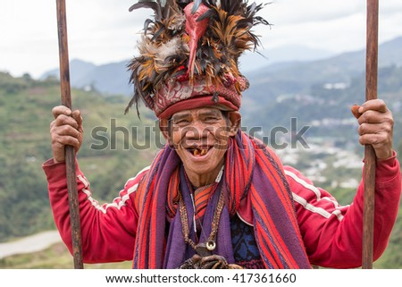 BANAUE, PHILIPPINES - JANUARY 24, 2014 : Portrait old Filipino man of Ifugao mountain tribes in national dress next to rice terraces. Ifugao - the  mountain people in the Philippines. - stock photo