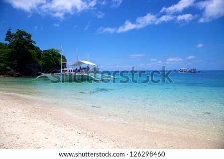 Banca boat on a white sand tropical beach on Malapascua island, Philippines - stock photo