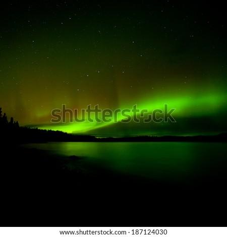 Band of aurora borealis or Northern Lights illuminates dark starry night sky over Lake Laberge, Yukon Territory, Canada - stock photo