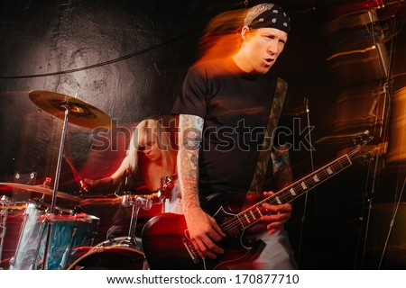 Band playing on a stage. Male guitarist and female drummer. Shot with strobes and slow shutter speed to create lighting atmosphere and blur effects. Slight motion blur on performers. - stock photo