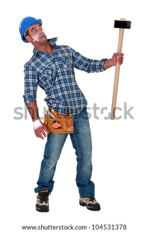 Bandaged construction worker wary of a sledgehammer - stock photo