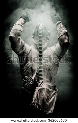 bandaged men in the gas mask on the black background surrounded by smoke and looking at the sky, survival soldier after apocalypse. - stock photo