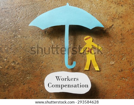 bandaged paper man under umbrella with Workers Compensation note below  - stock photo