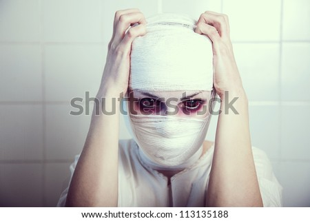 Bandaged victim of genetic experiment embracing herself, red eyes are real contact lenses - stock photo