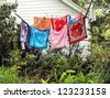Bandanas or bandannas of different bright colors drying in the sun on a dilapidated clothes line in an overgrown yard. - stock photo