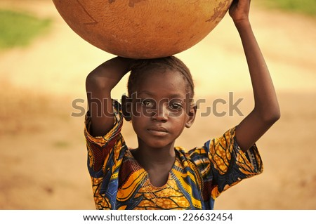 Bandiagara, Mali, Africa - August 27, 2011  Dogon tribe girl carrying water home - stock photo