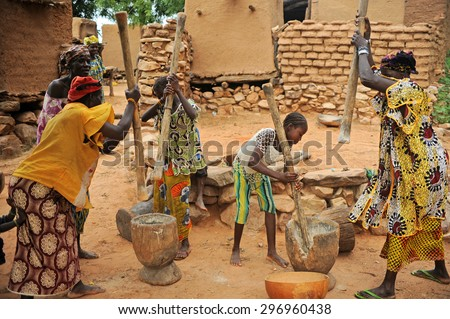 BANDIAGARA, MALI, AFRICA - AUGUST, 28, 2011 Dogon woman sings while other women grind millet - stock photo