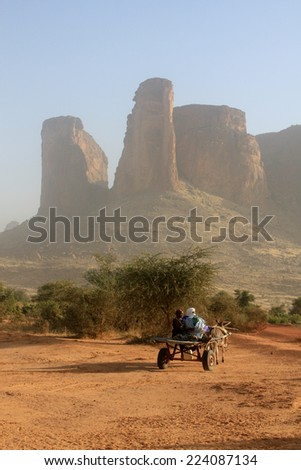 BANDIAGARA, MALI - SEPTEMBER 30, 2008:  African family on a cart pulled by a donkey in the desert in bandiagara in the Mopti region in Mali on september 30, 2008, Bandiagara, Mali - stock photo