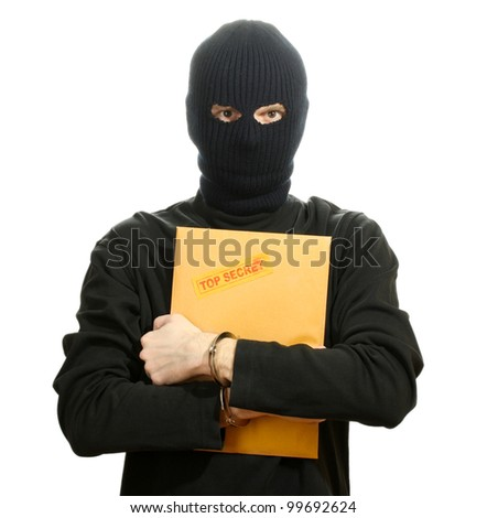 Bandit in black mask in handcuffs with top secret envelope isolated on white - stock photo