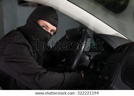 Bandit preparing to leave with a stolen car. - stock photo