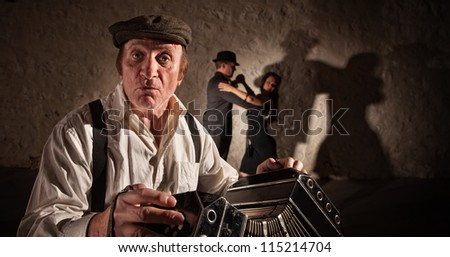 Bandoneon player singling with dancers in background - stock photo