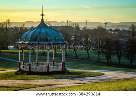 Bandstand in Dunfermline Park just after Sunrise with wind turbine and Queensferry Crossing towers in the distant background - stock photo
