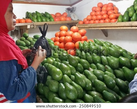 BANDUNG, WEST JAVA, INDONESIA- SEPTEMBER 15, 2014 : Unidentified Indonesian woman sells avocados and pumpkins in Bandung, Indonesia. Bandung is a city located in the West Java island. - stock photo