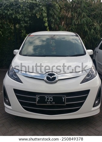 BANDUNG, WEST JAVA, INDONESIA- SEPTEMBER 15, 2014 : Unidentified Mazda car model parked in front of a popular tourist attraction site in Bandung, Indonesia. Mazda Motor Corp is a Japanese car maker. - stock photo