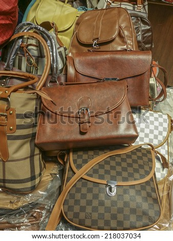 BANDUNG, WEST JAVA ISLAND, INDONESIA - SEPTEMBER 16, 2014: Large collection of famous fake handbags on display at one of the shopping centres in Bandung. The fake handbags are widely sold cheaply here. - stock photo