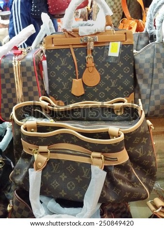 BANDUNG, WEST JAVA ISLAND, INDONESIA -SEPTEMBER 16, 2014: Large collection of famous fake handbags on display at one of the shopping centres in Bandung. The fake handbags are widely sold cheaply here. - stock photo