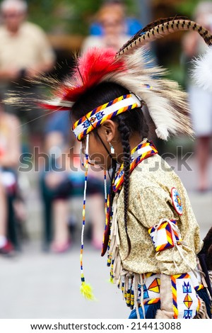 BANFF, CANADA - JUL 3: A young native Blackfoot Indian dancer performs her native dance during the Banff Summer Arts festival July 3, 2014. The Festival is the longest running arts festival in Canada.