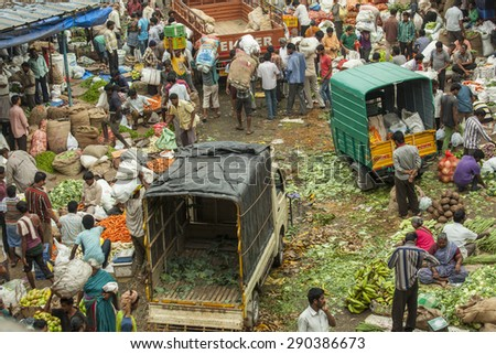 BANGALORE, INDIA - May 27, 2014: Aerial view of the busy city market, vendors sell produce, vehicles move through the crowd.