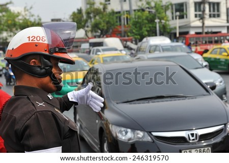 BANGKOK - APR 10: A police officer directs traffic on a busy city centre road on Apr 10, 2013 in Bangkok, Thailand. The Thai capital is notorious for its congested roads and pollution.