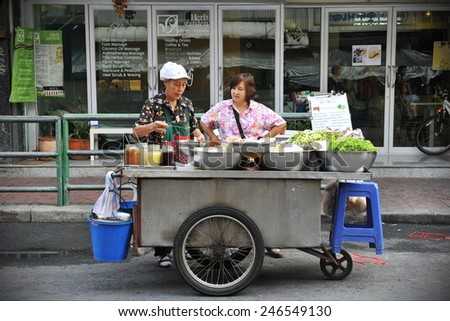 BANGKOK - APR 12: A vendor serves a customer on a city centre street on Apr 12, 2013 in Bangkok, Thailand. Government statistics indicate 16,000 registered street vendors in the Thai capital. - stock photo