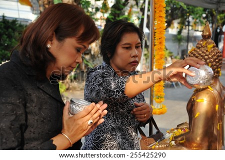 BANGKOK - APR 13: Temple goers pour water over a Buddha statue at a temple during a merit making ceremony to mark the traditional Thai New Year or Songkran on Apr 13, 2014 in Bangkok, Thailand. - stock photo