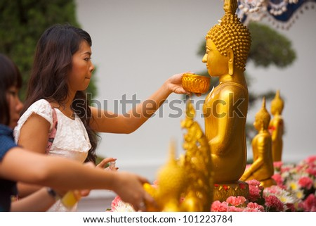 BANGKOK - APRIL 9, 2011: A Buddhist Thai woman cleans and perfumes a Buddha statue to gain merit, an annual ritual for the holiday of Songkran or Thai New Year on April 9, 2011 in Bangkok - stock photo