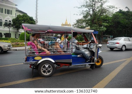 BANGKOK - APRIL 12: A tuk tuk taxi transports passengers on a road in the Khao San area on Aug 12, 2013 in Bangkok, Thailand. Tuk tuks can be hired from as little as $1 or B30 a fare for shop trips. - stock photo