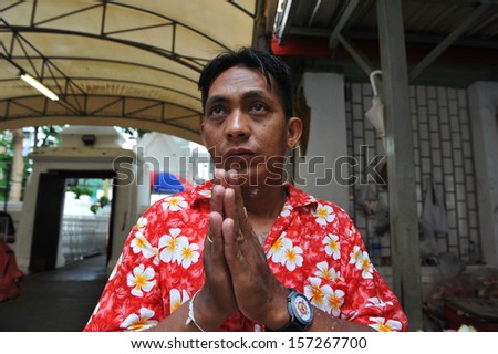 BANGKOK - APRIL 12: An unidentified man prays while taking part in a merit making ceremony at a Buddhist temple during Songkran, or Thai New Year, celebrations on April 12, 2013 in Bangkok, Thailand. - stock photo