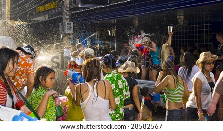 BANGKOK - APRIL 13: People roam the streets and drench each other and passersby with water at Songkran (Thai new year/water festival) April 13, 2009 in Bangkok, Thailand. - stock photo