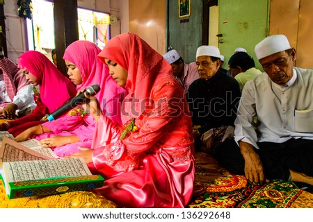 BANGKOK - APRIL 13 : Unidentified children reading Quran for ceremony in Graduation of the Quran on April 13, 2013 in Bangkok, Thailand.