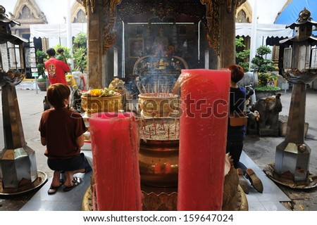 BANGKOK - APRIL 12: Unidentified people attend a Buddhist temple while taking part in traditional celebrations of the Thai New Year, or Songkran, on April 12, 2013 in Bangkok, Thailand. - stock photo