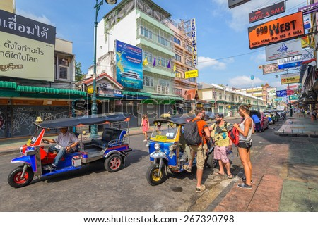 BANGKOK - April 6: Unidentified tourists bargain with Thai native taxi or Tuk Tuk at Khao San Road on April 6, 2015 in Bangkok, Thailand. This road is popular among backpacker. - stock photo