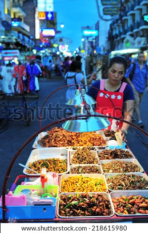 BANGKOK - AUG 30: A street vendor sells fried cockroaches and other insects to tourists on Khao San Road on Aug 30, 2014 in Bangkok, Thailand. There is 16,000 registered street vendors in Bangkok.  - stock photo