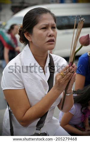BANGKOK - AUG 2: A woman prays at a temple during a ceremony to mark Buddhist lent on Aug 2, 2012 in Bangkok, Thailand. Buddhist lent or Phansa marks the rainy season when monks retreat to temples.  - stock photo