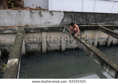 BANGKOK - AUG 16: An unidentified man fishes in a canal in central Bangkok on Aug 16, 2011 in Bangkok, Thailand. The Social Development Ministry estimates up to 4,000 homeless in Bangkok.