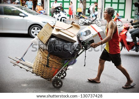 BANGKOK - AUG 23: An unidentified man transports discarded materials on Aug 23, 2012 in Bangkok, Thailand. Poverty remains a major problem in Thailand with the average wage under B200 or $4 a day. - stock photo