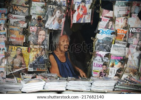 BANGKOK - AUG 21: An unidentified shopkeeper mans a magazine store on Aug 21, 2013 in Bangkok, Thailand. The Thai publishing industry is in decline due to falling ad revenues and readership. - stock photo