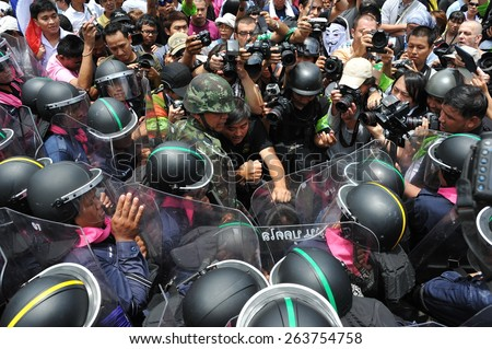 BANGKOK - AUG 7: Protesters confront riot police at a barricade as press photographers jostle for position during an anti government rally near the Thai parliament on Aug 7, 2013 in Bangkok, Thailand. - stock photo