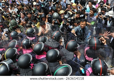 BANGKOK - AUG 7: Protesters confront riot police at a barricade near the Thai parliament during an anti government rally on Aug 7, 2013 in Bangkok, Thailand. About 3,000 protesters joined the rally. - stock photo