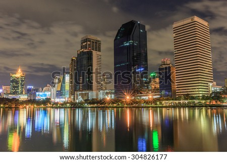 BANGKOK - AUGUST,10 : Cityscape view of modern buildings at Benjakitti garden at twilight time where have the light of the lamps shining on the pool and buildings.THAILAND AUGUST,10 2015